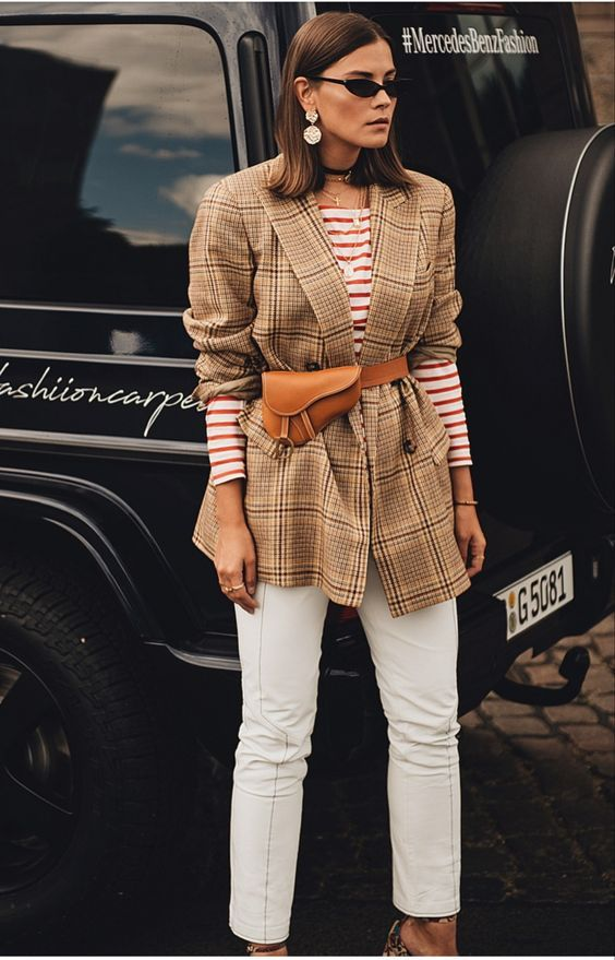 a striped long sleeve top, a tan plaid oversized blazer, an amber waist bag, white trousers and statement earrings