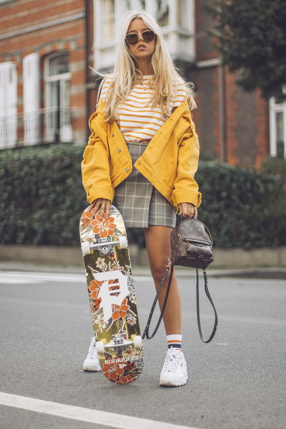 a striped t-shirt, a grey plaid wrap mini skirt, white trainers and striped socks, a yellow denim jacket and a backpack