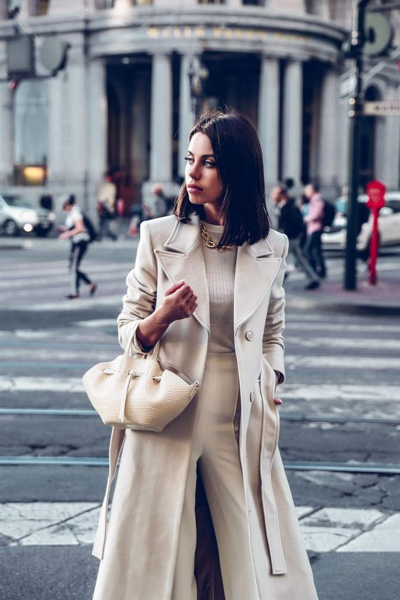 a stylish neutral look with a top, trousers, a coat and a pretty small bag that makes a statement with its shape