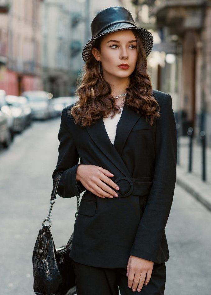 a super chic and classic look with a black pantsuit with a belt, a black bag, a black bucket bag and statement necklaces and earrings