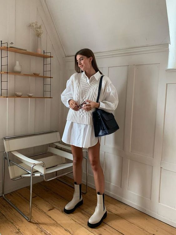 a super trendy work outfit with a white shirtdress, a white V-neck vest, white Chelsea boots and a black bag