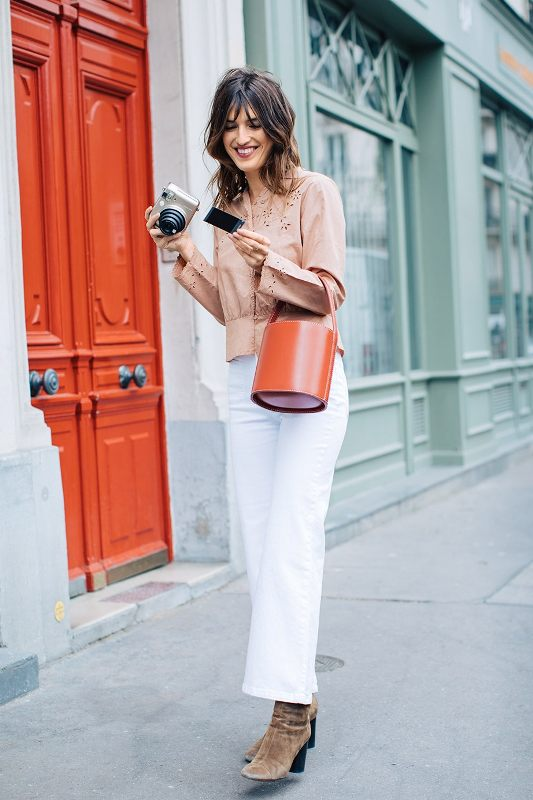 a tan perforated shirt, white trousers, tan suede boots and an orange bucket bag to add a bit of color