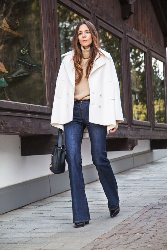 a tan sweater, navy flare jeans, a white cropped coat and a black bag for a cold fall or winter day