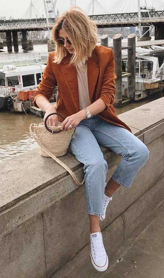 a tan t-shirt, light blue jeans, white sneakers, a rust-colored velvet blazer and a woven mini bag