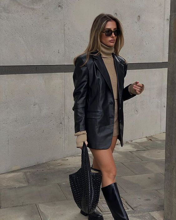 a tan turtleneck and a mini skirt, a black leather blazer, rider boots and a black bag for this fall