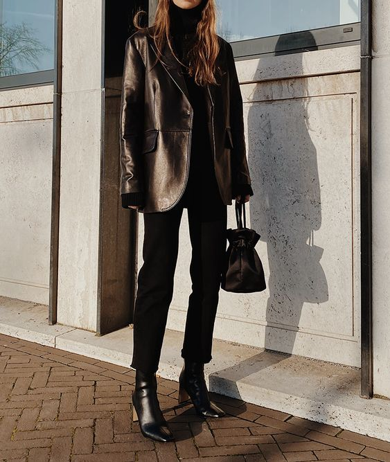 a total black outfit with a turtleneck, jeans, boots, a leather blazer and a small bag is cool