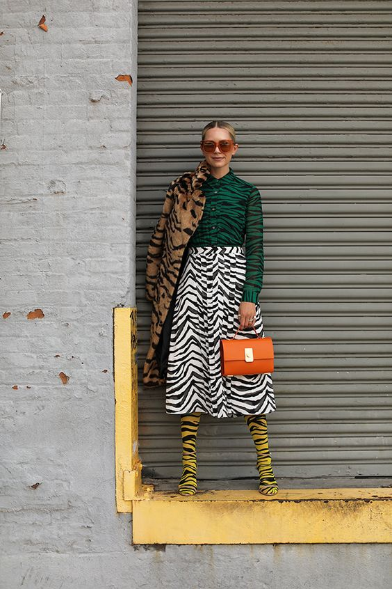 a total zebra print look with a green shirt, a midi white skirt, yellow boots, and faux fur coat and an orange bag