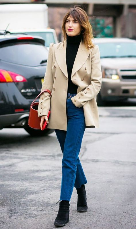 a very simple fall outfit with a black turtleneck, a tan refined blzer, bold blue jeans, black boots and a red bucket bag