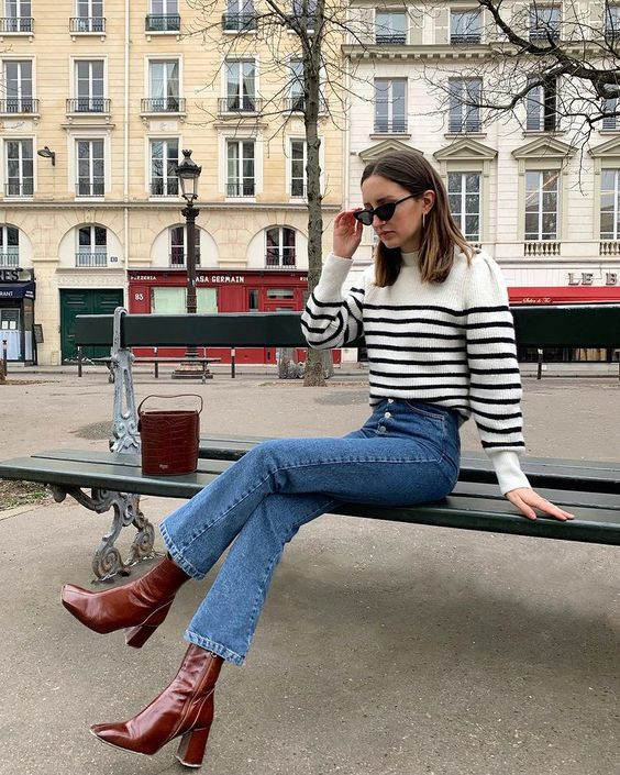 a white and black striped sweater, blue jeans, burgundy block heel boots and a matching bucket bag