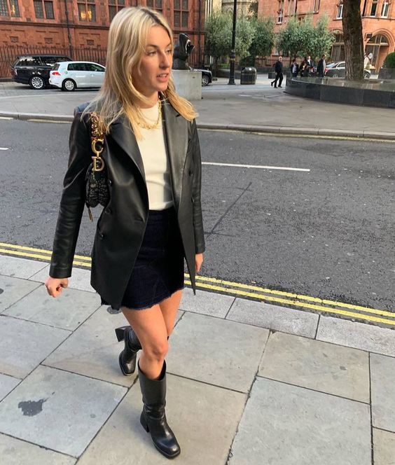 a white crop top, a black denim mini, black boots, a leather blazer and a small bag on chain with monograms