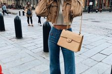 a white crop top, a brown denim cropped jacket, blue flare jeans, white trainers and a tan bag