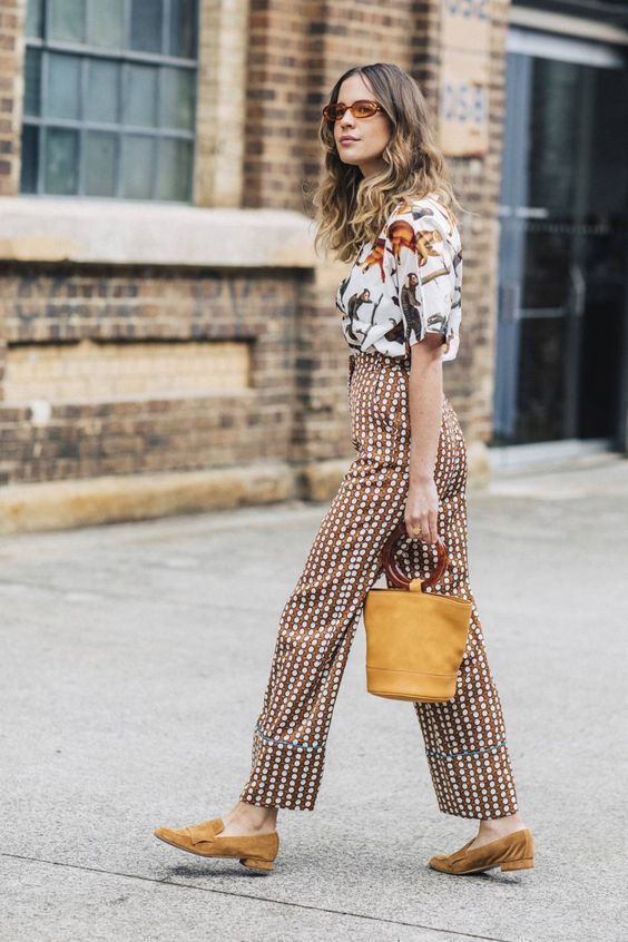 a white fauna print t-shirt, rust polka dot pants, mustard loafers and a matching bucket bag for a catchy look