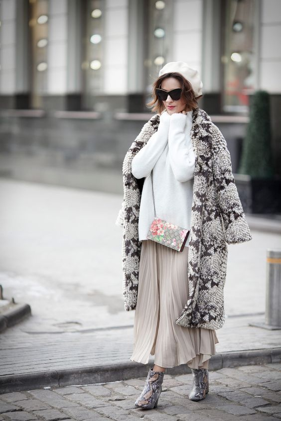 a white oversized sweater, a neutral pleated maxi, a snakeskin print fur coat, snakeskin print booties and a white beret