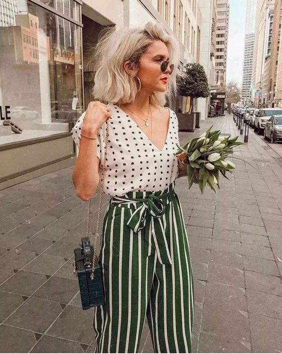 a white polka dot shot sleeve shirt, green striped paper bag waist trousers and a black bag plus layered necklaces