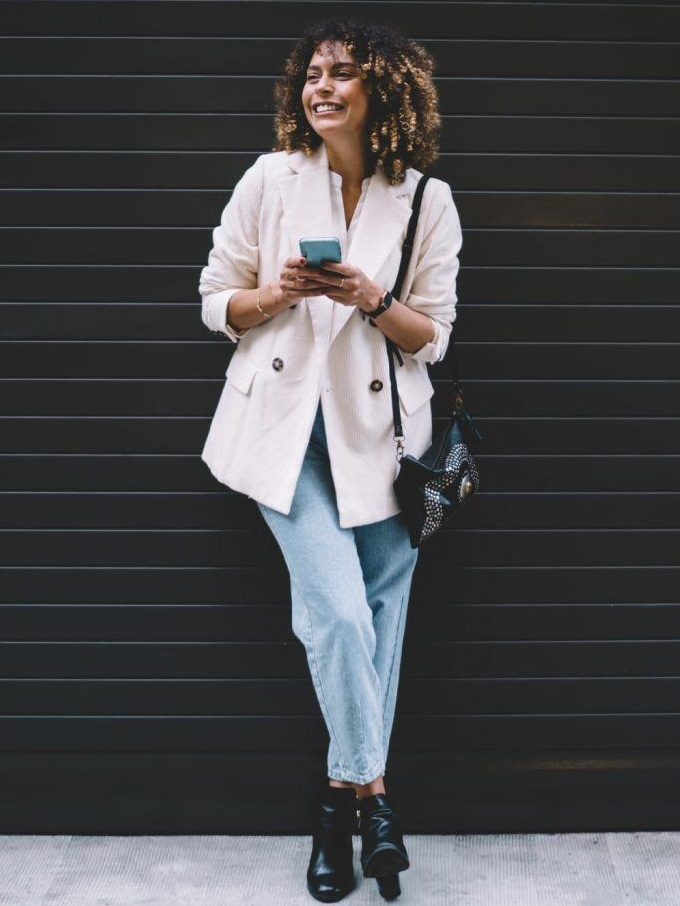 a white shirt, a white oversized corduroy blazer, blue cropped jeans, black booties and a black embellished bag