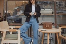 a white t-shirt, a black blazer, blue high waisted flare jeans and black sneakers plus a brown bag