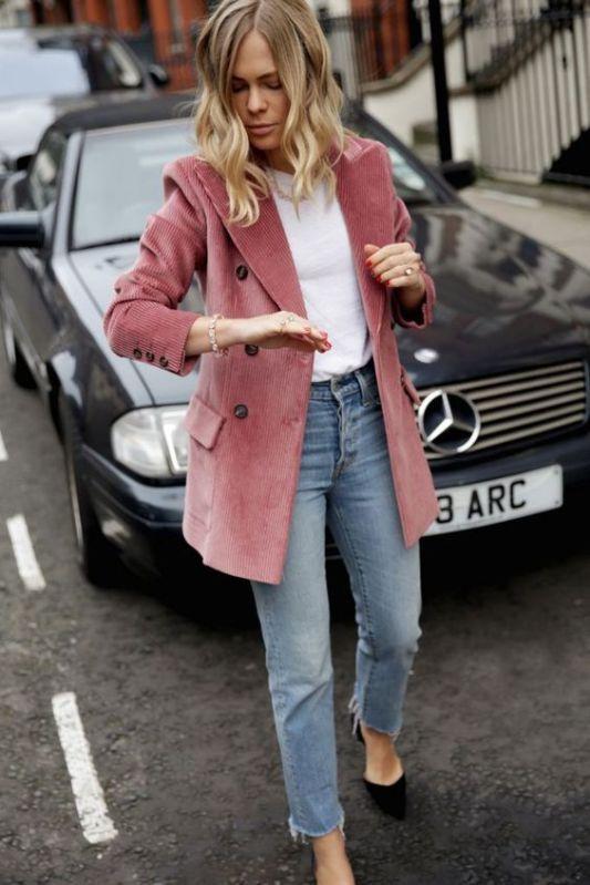 a white t-shirt, an oversized pink corduroy blazer, blue slim leg jeans, black shoes