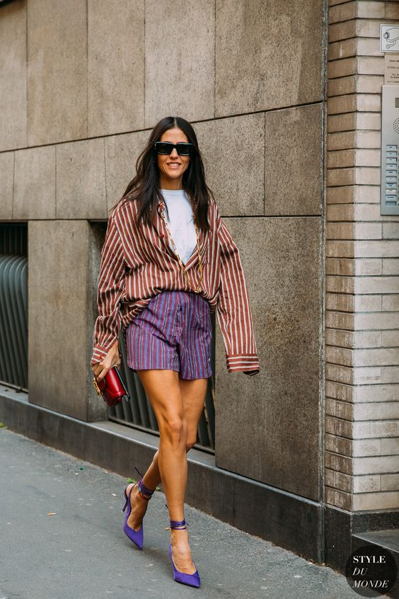 a white t-shirt, an oversized rust striped shirt, purple striped mini shorts, purple shoes and a red bag for summer