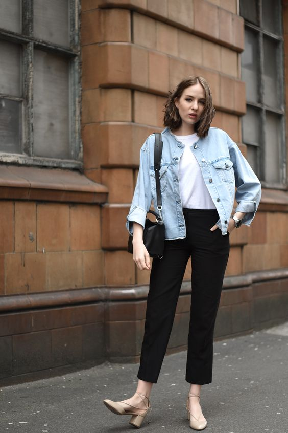 a white t-shirt, black cropped trousers, a light blue denim jacket, tan lace up shoes and a black bag