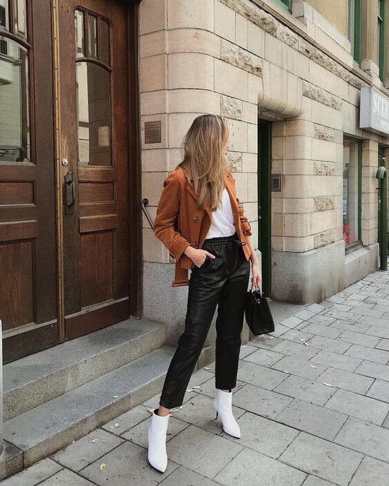 a white t-shirt, black leather trousers, white booties, a black bag, a rust-colored cropped coat for work