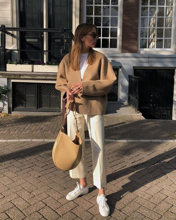 a white t-shirt, creamy trousers, white sneakers, a tan cardigan and a matching bag for the fall