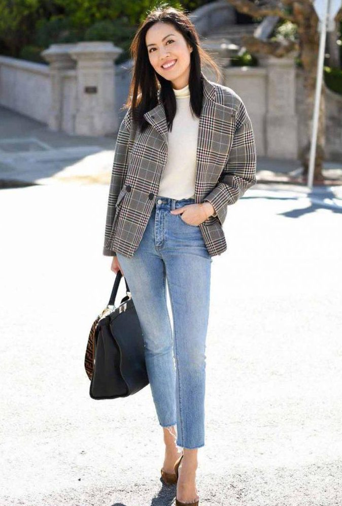 a white turtleneck, a grey plaid blazer, blue cropped jeans, rust-colored shoes and a large comfy bag