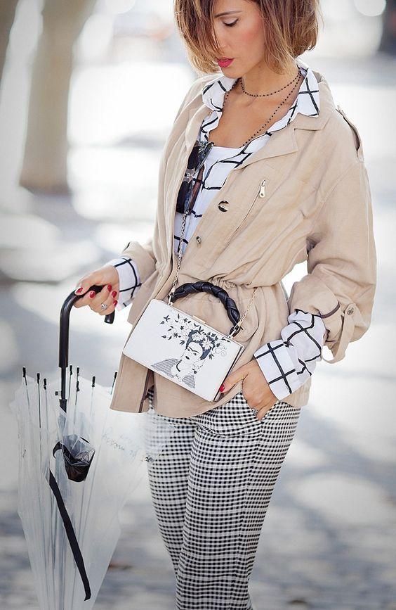 a white windowpane shirt, plaid trousers, a tan jacket and a black and white Frida Kahlo bag