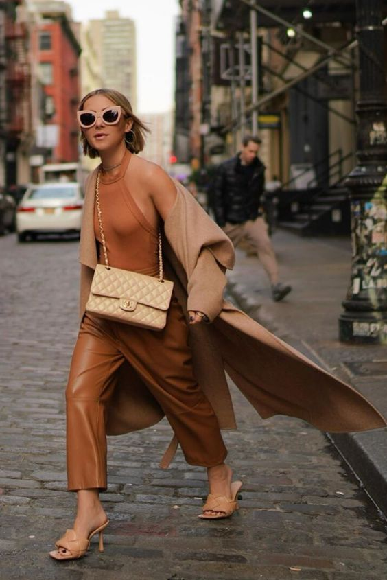 an edgy look with a rust-colored vest, leather trousers, tan heels, a tan bag and a tan coat is very refined
