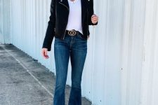 an everyday look with a white t-shirt, navy flare jeans, a black leather jacket and white boots is all cool