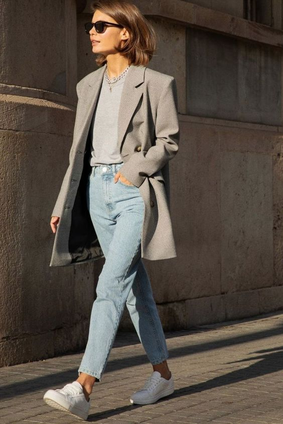 an everyday outfit with a gree t-shirt, a grey oversized blazer, blue jeans, white sneakers and a chain necklace