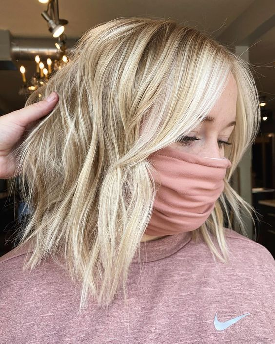 beautiful blonde hair with icy blonde balayage, with waves and curtain bangs looks very chic and very stylish