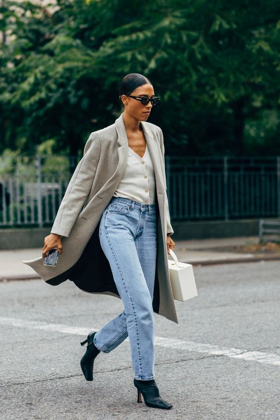 blue barrel jeans, black boots, a white cardigan as a shirt, a grey midi coat and a white suitcase-style bag