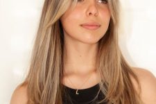gorgeous long hair with warm blonde balayage and with curtain bangs, with much texture is a very stylish idea to rock