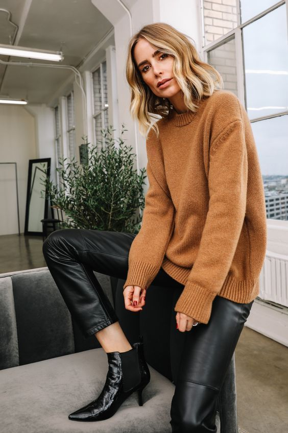a beige sweater, black leather trousers and black lacquer Chelsea boots with kitten heels fore amazing