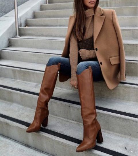 a beige sweater, blue skinnies tucked into brown knee high boots, a beige blazer and a brown printed clutch