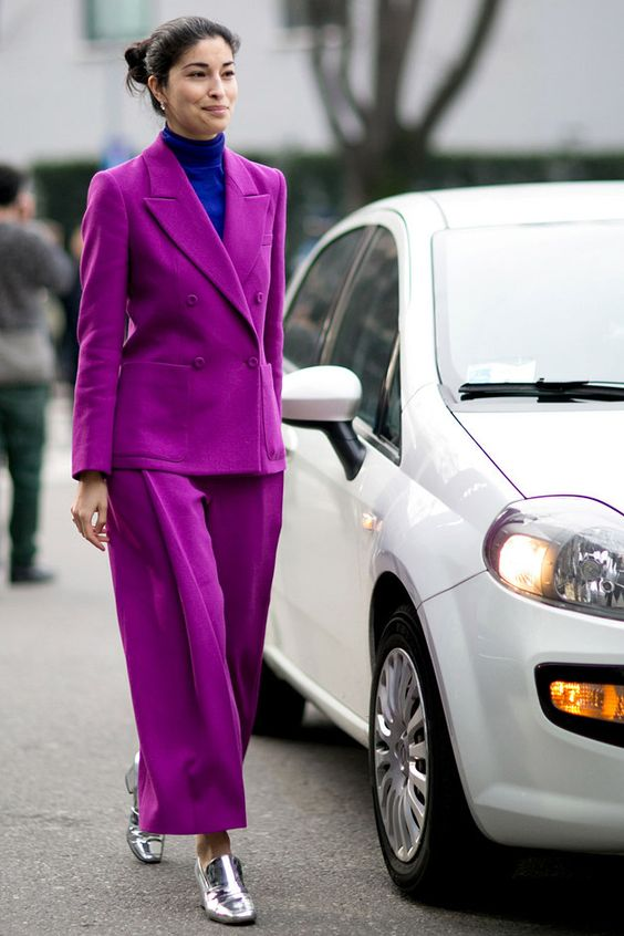 a bold fall work outfit with an electric blue turtleneck, a purple pantsuit with wide leg trousers, silver loafers