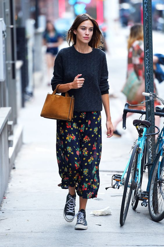 a black floral midi skirt, a black jumper, black sneakers, a rust-colored suede bag for every day