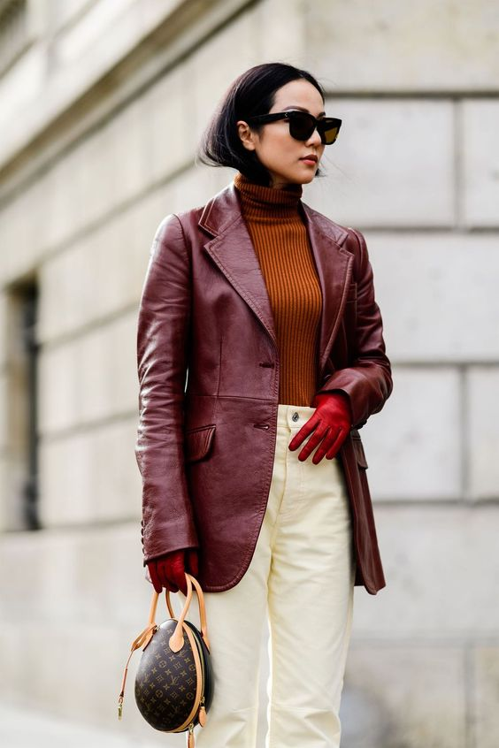 a trendy fall work outfit with a rust-colroed turtleneck, white jeans, a burgundy leather blazer, red gloves and a printed bag