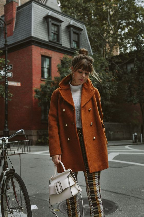 a white turtleneck, plaid trousers, a rust-colored short coat, a creamy bag and statement earrings