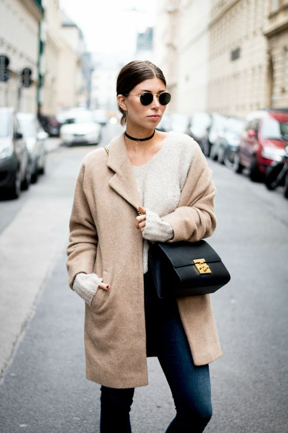a casual look with a neutral top, navy jeans, a tan short coat, a black bag and a choker
