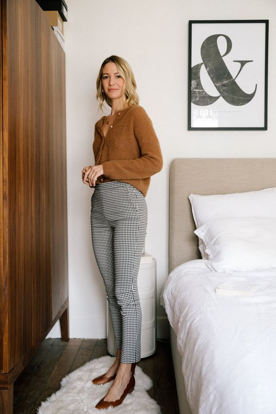 a French chic fall work look with a rust-colored cardigan as a shirt, plaid flare trousers, rust-colored shoes