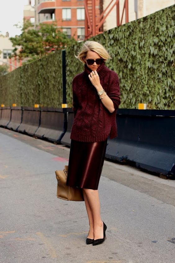 a burgundy turtleneck sweater, a shiny vinyl skirt, black shoes and a tan tote for work