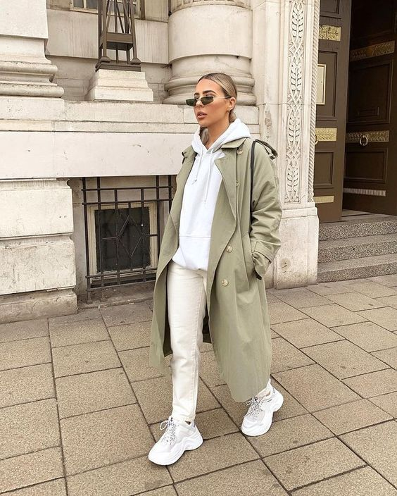 a grey hoodie, white jeans, white trainers, an olive green trench and a black bag for a super comfy college look