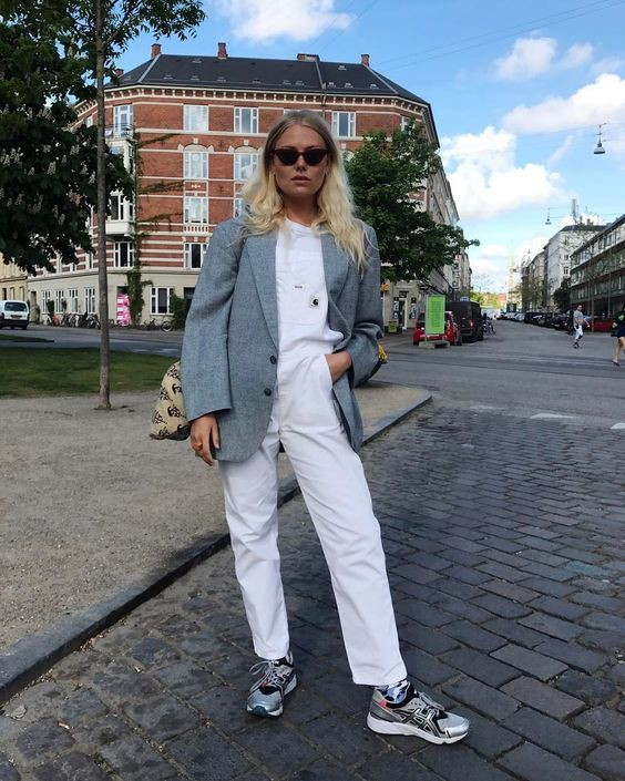 a grey sweatshirt, white trousers, grey printed trainers, a grey blazer and a printed bag for the fall