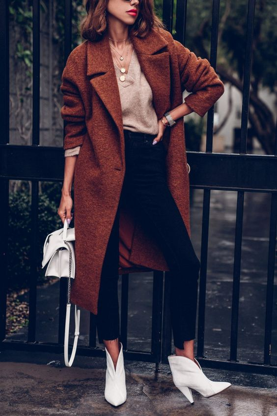 a neutral V-neck jumper, black jeans, white boots, a rust-colored midi coat, a white bag and layered necklaces