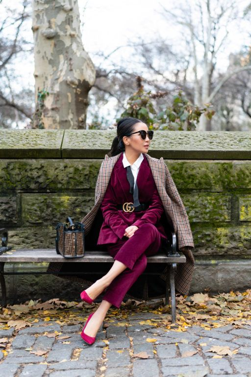 a chic work outfit with a burgundy velvet pantsuit, pink shoes, a white shirt, a black belt and a plaid coat