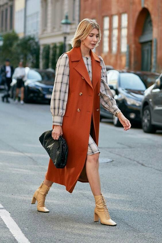 a plaid shirtdress with puff sleeves, tan lace up booties, a rust sleeveless coat and a black clutch for work