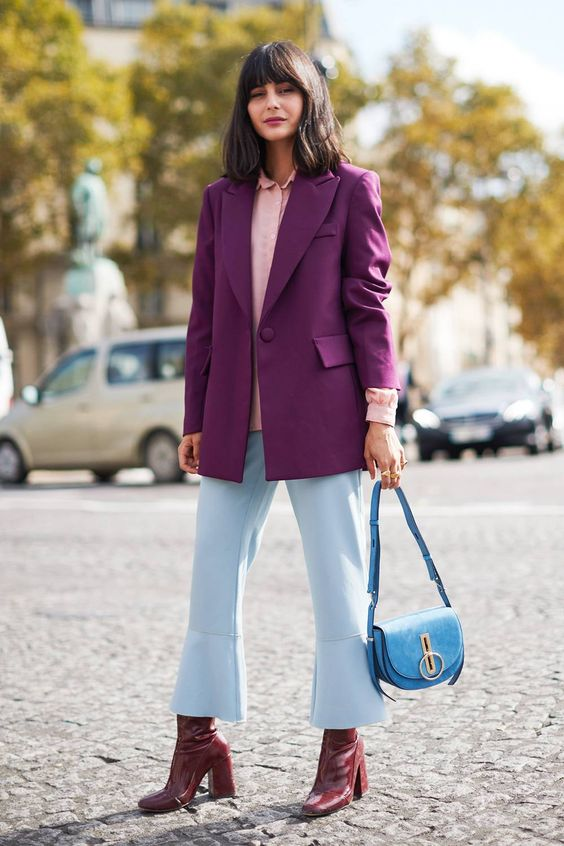 an elegant fall work outfit with a pink shirt, a purple blazer, blue flare pants, purple boots and a blue bag