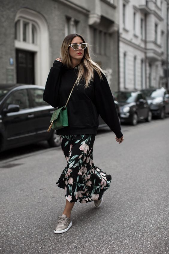 a black floral maxi dress, a black sweatshirt over it, metallic sneakers and a bold green bag for a fresh and comfy look