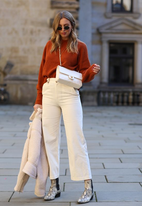 a rust-colored cahsmere jumper, white jeans, snakeskin print Chelsea boots, a white bag to create a constrasting look